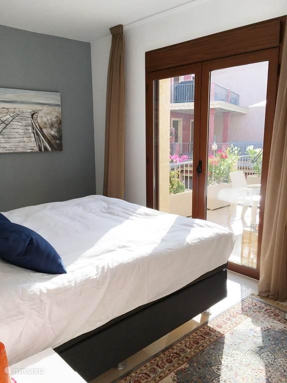 Slaapkamer met 2 persoonsbed met inloopkast, badkamer met douche, wastafels en toilet.