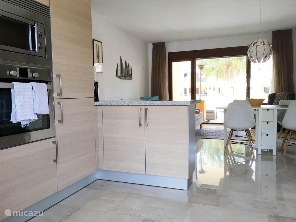 De woonkamer met open keuken, zithoek en eethoek. Schuifpui naar het dakterras.