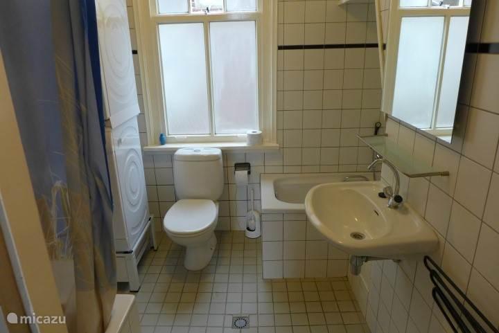 Badkamer met douche en bad