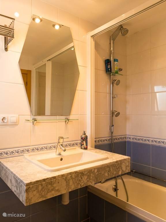 Badkamer en suite met douche en bad.