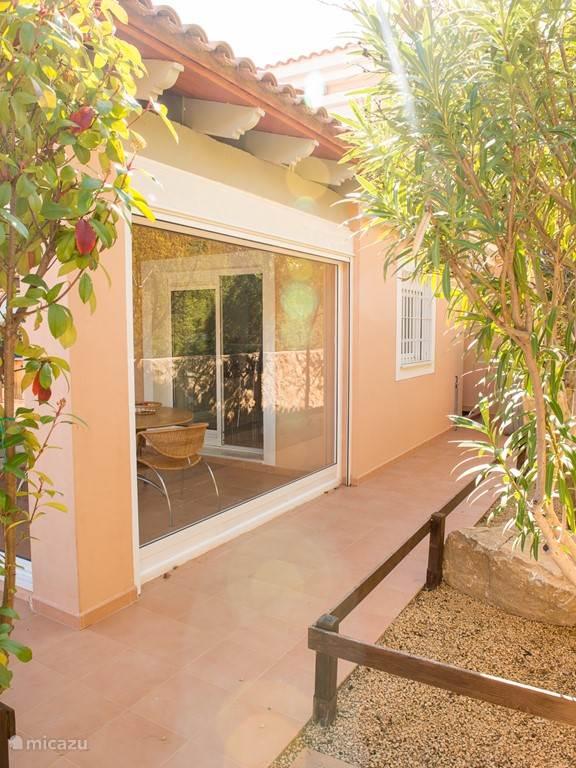 Zijaanzicht (patio en keuken) van Casa Irlanda met uiterst rechts in de nis de voordeur. De tuin is voorzien van tuinverlichting.