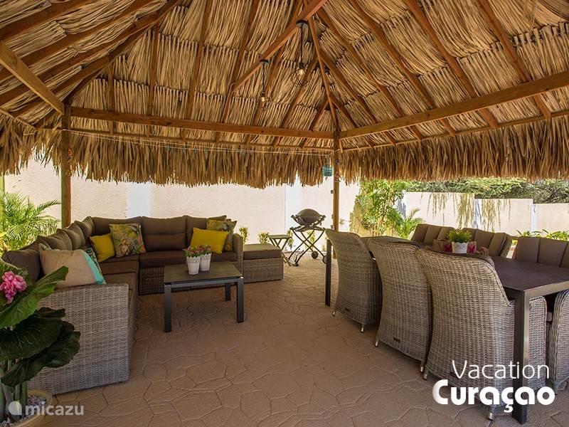 Grote overdekte palapa met loungeset, 6-persoons eettafel, electrische barbeque en uitzicht op het zwembad. Heerlijk op de wind gelegen.