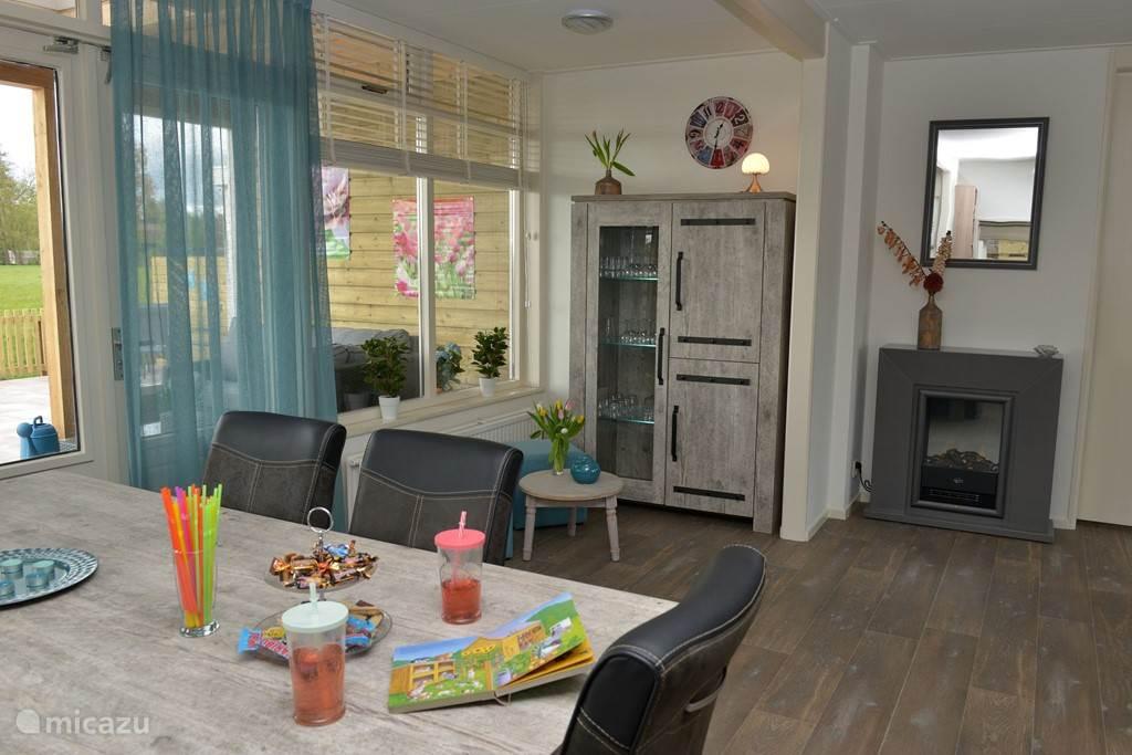 Onze warme en sfeervolle woonkamer met elektrisch haardje, tv en digitenne