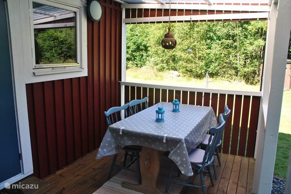 De achterkant van het huisje met de gezellige overdekte open veranda.