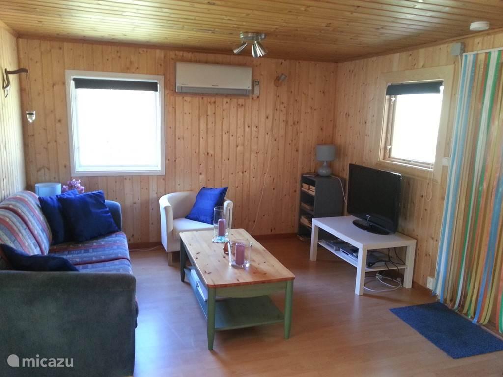 De gezellige woonkamer met zithoek, slaapbank en tv.