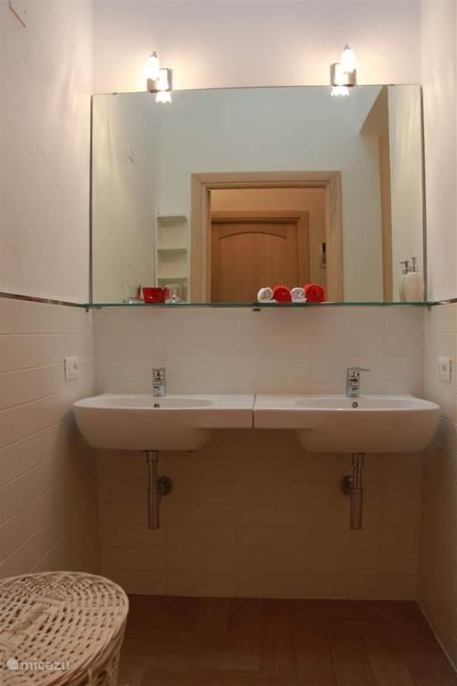 Badkamer met:  - dubbele wastafel -douche, toilet en bidet.