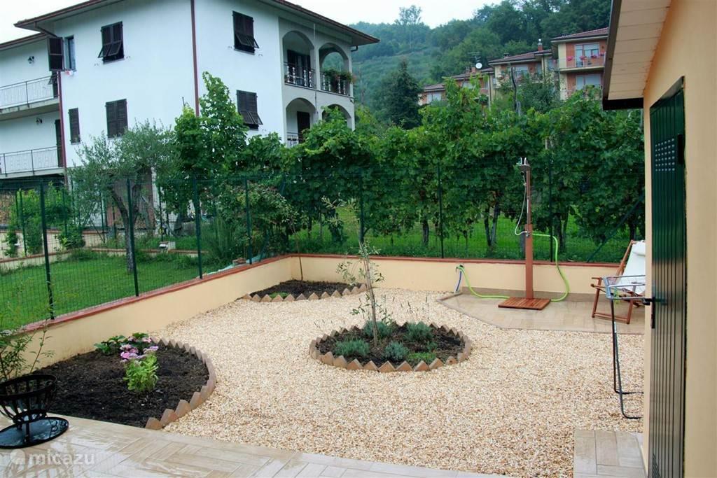 Veranda achter het huis met tuindouche en zicht op druivenranken.