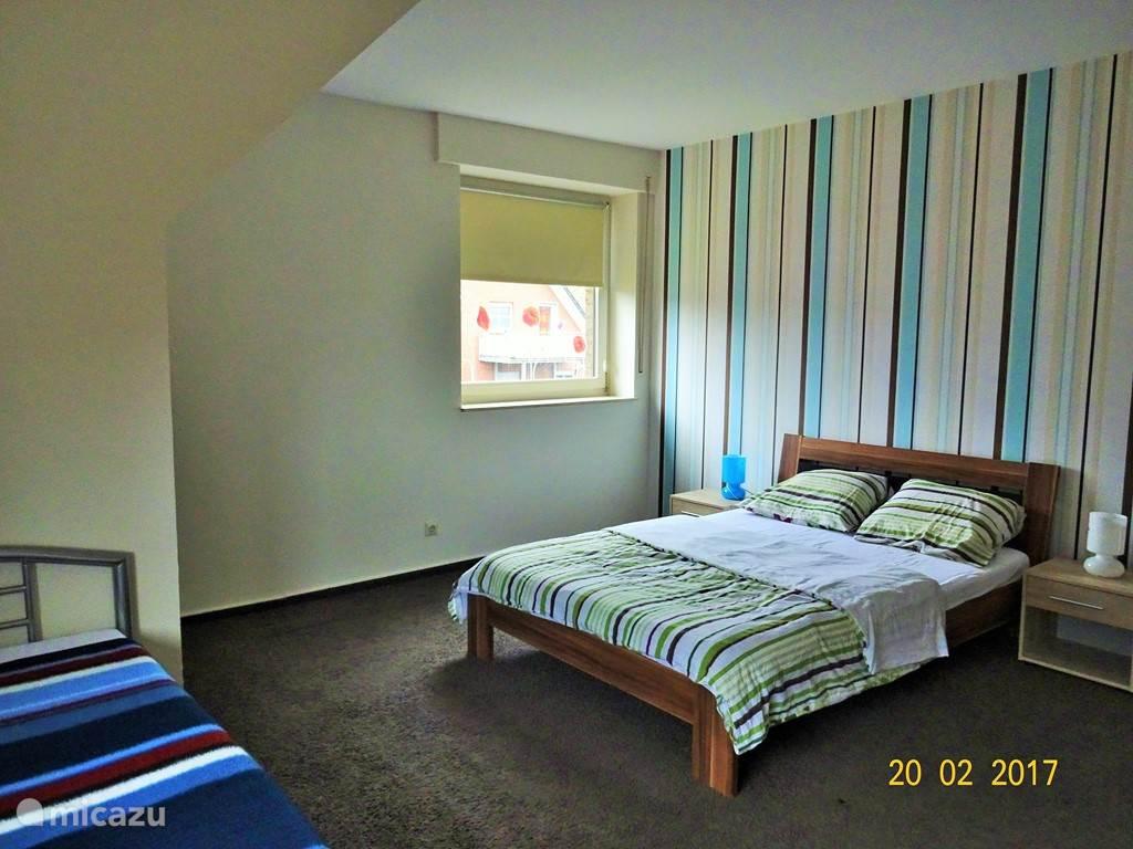 Deze grote slaapkamer heeft een 2- en een 1-persoons bed.