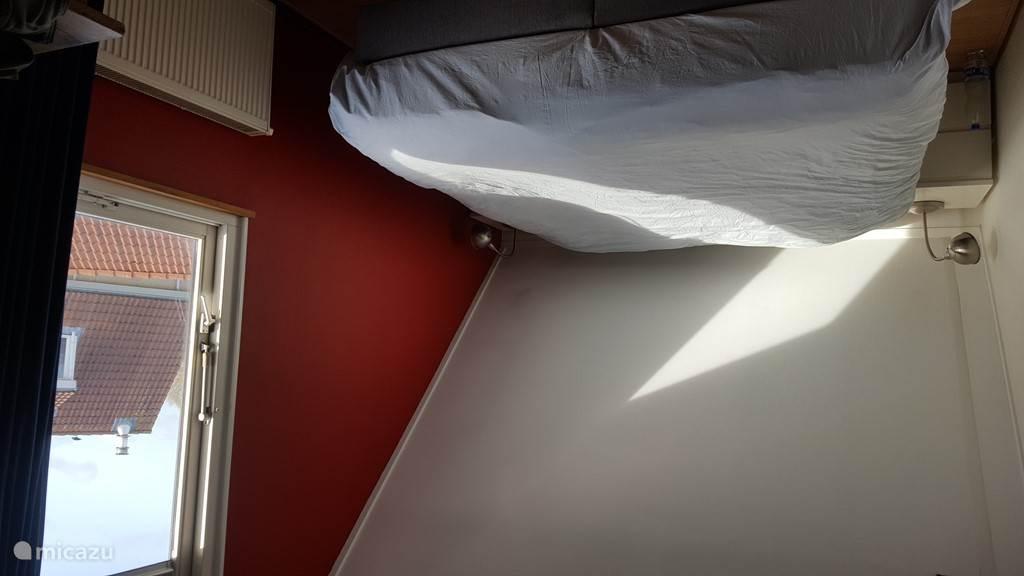 Slaapkamer met airco en groot bureau.