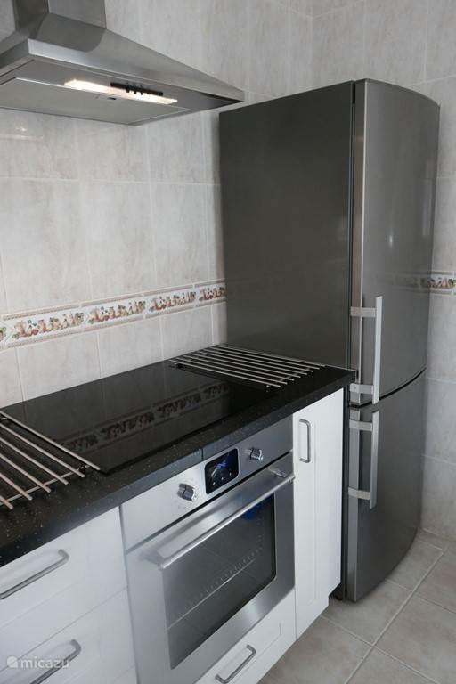Keuken met inductiekookplaat, oven, koelvriescombinatie en vaatwasser