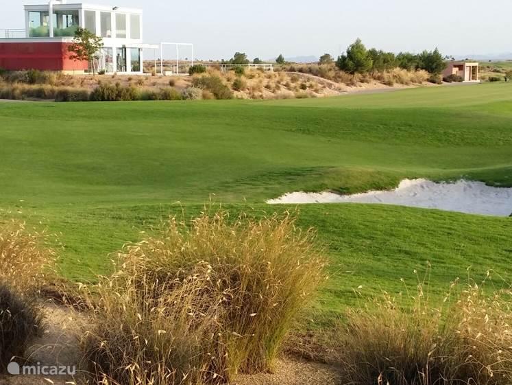 Uitzicht vanaf het terras op het clubhuis en de golfbaan.