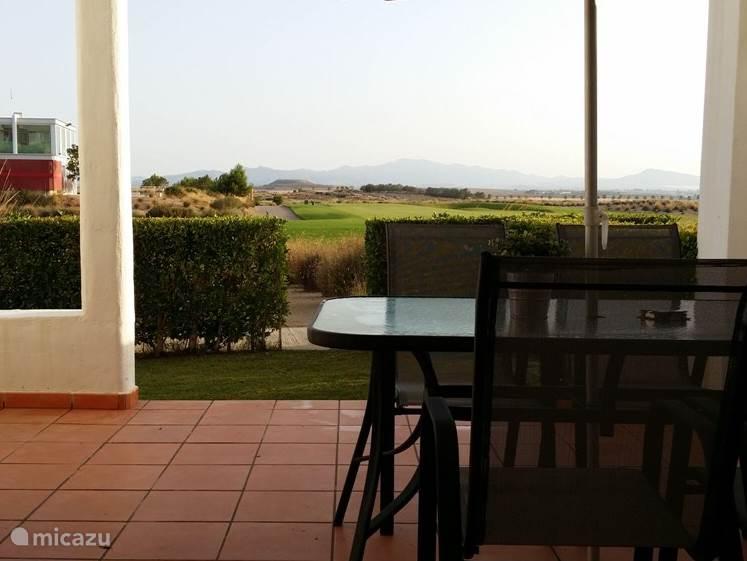 Uitzicht vanuit de woonkamer op het terras, het clubhuis en de golfbaan.