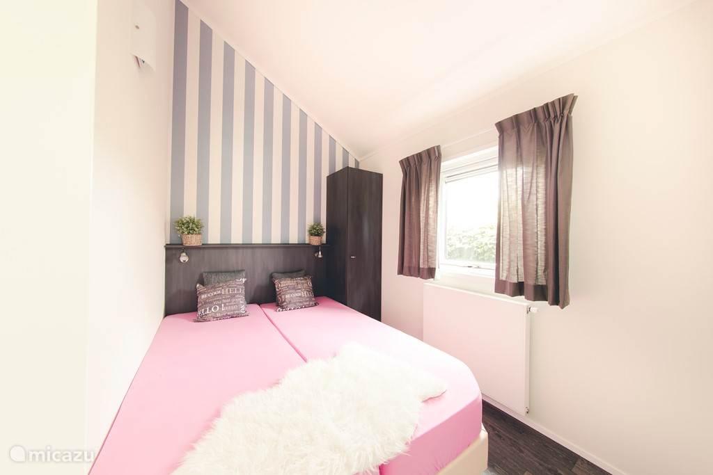Knusse ouderslaapkamer met comfortabele bedden.