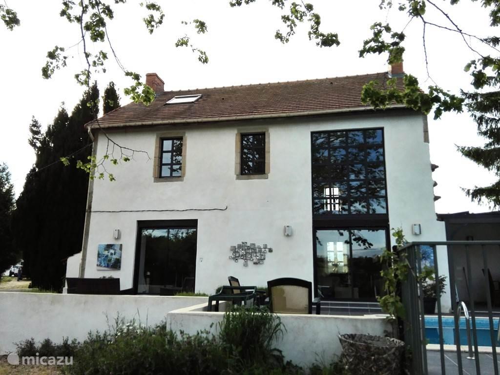 Het huis heeft grote schuifdeuren naar het terras