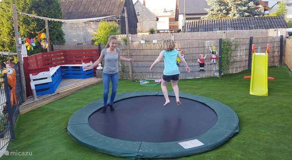 Speelplaats met trampoline in de tuin.