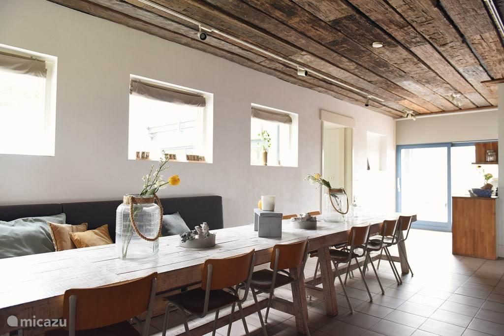 Een lange ruime tafel waar iedereen aan kan dineren, borrel, kletsen en lachen