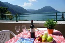 Uitzicht vanaf het balkon over het meer van Lugano en de bergen op de achtergrond.