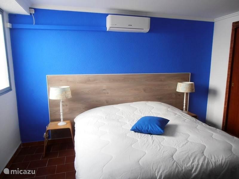 master slaapkamer met inbouw kasten en airco en raam naar binnenplaats.