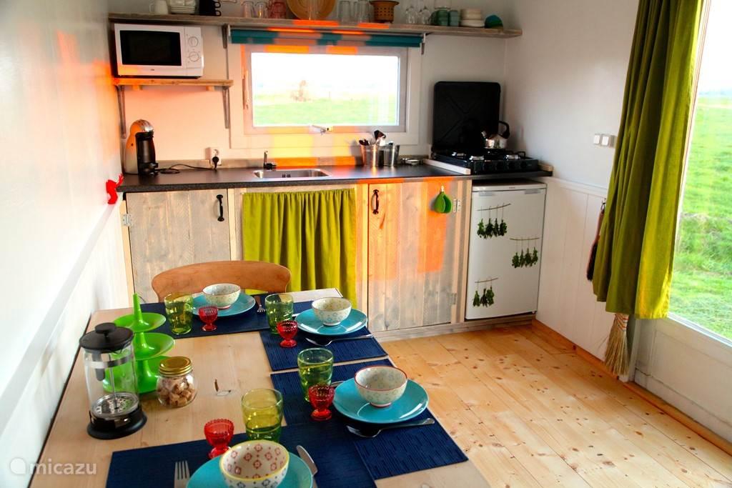 Eettafel en keuken. De keuken is voorzien van een kookplaat, koelkast en magnetron.