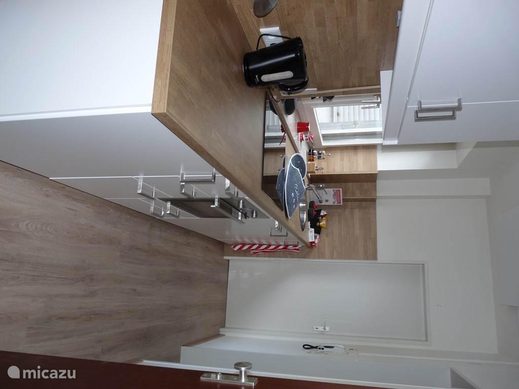 Moderne keuken met vaatwasser, combi oven/magnetron en koelkast met vriesvak.