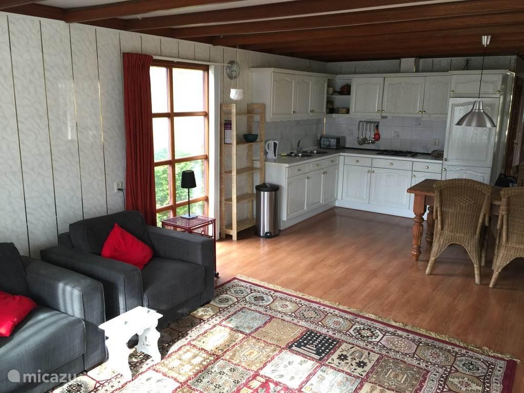 Ruime woonkamer en grote open keuken met eettafel
