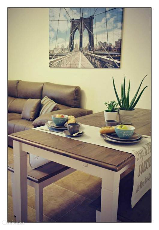 De gezellige leefruimte met eetplaats, salon, flatscreen tv, TV Vlaanderen, Wifi, Airco, groot schuifraam met toegang naar het terras.