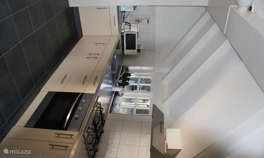 de keuken, voorzien van oven, magnetron, broodrooster, koelkast...