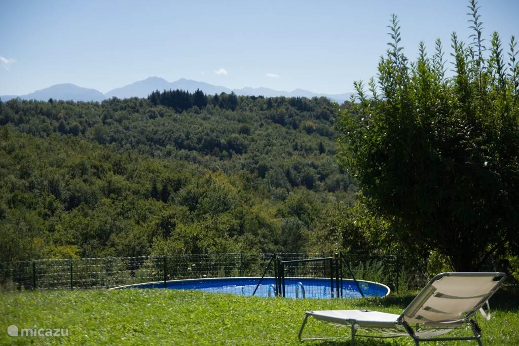 Het zwembad ligt op een tiental meters van het huisje, achter de bomen