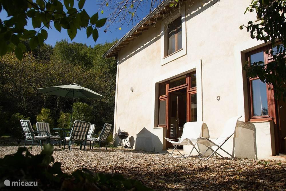 La Maisonnette heeft een groot terras, beschut door bomen, heggen en planten.