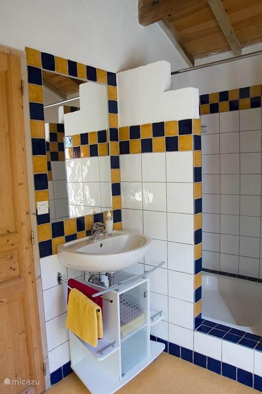 De badkamer met douche, toilet en wasbak.