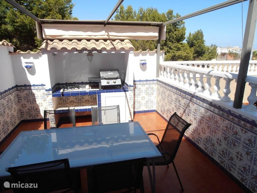 Terras achter het huis met BBQ en Paella Pan.