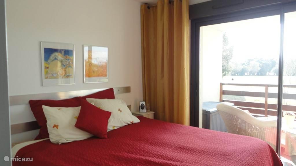 1e slaapkamer met 2 bedden van 90 x 200 en een linnenkast. Via een schuifdeur kun je naar het terras.