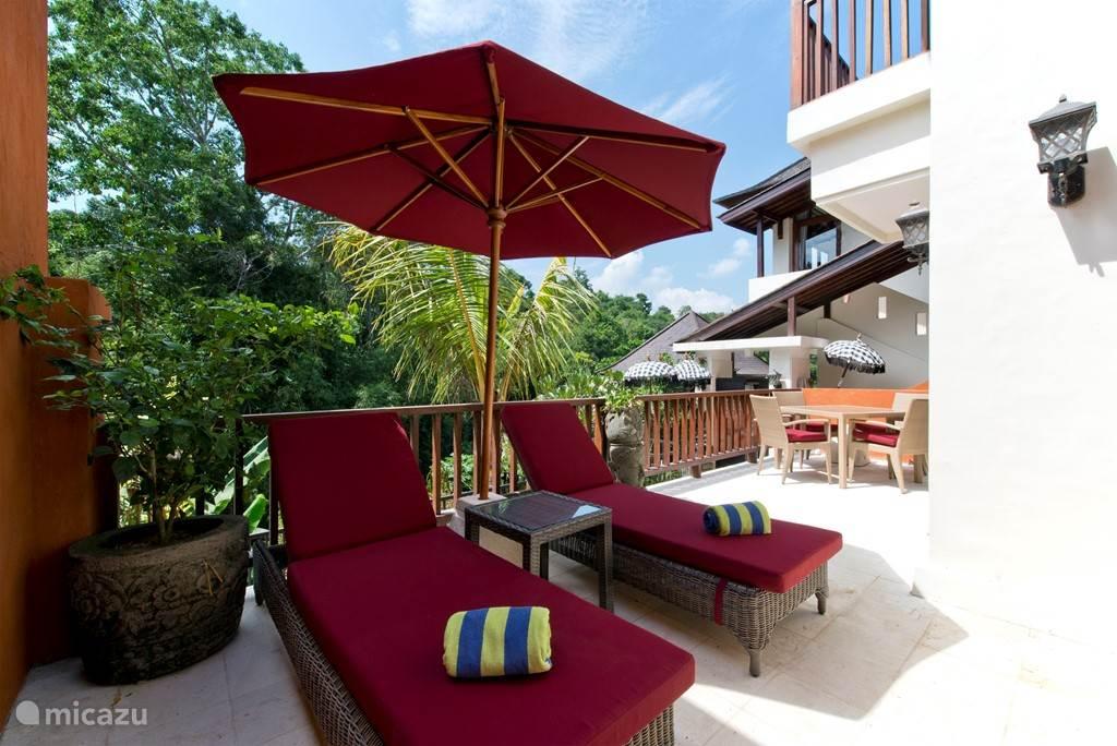 een heerlijk woonterras met ligstoelen...dichtbij de groene jungle