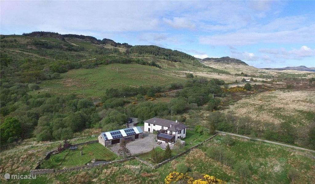 Het huis met op de achtergrond de heuvel waar Stronafian Community Forest ligt