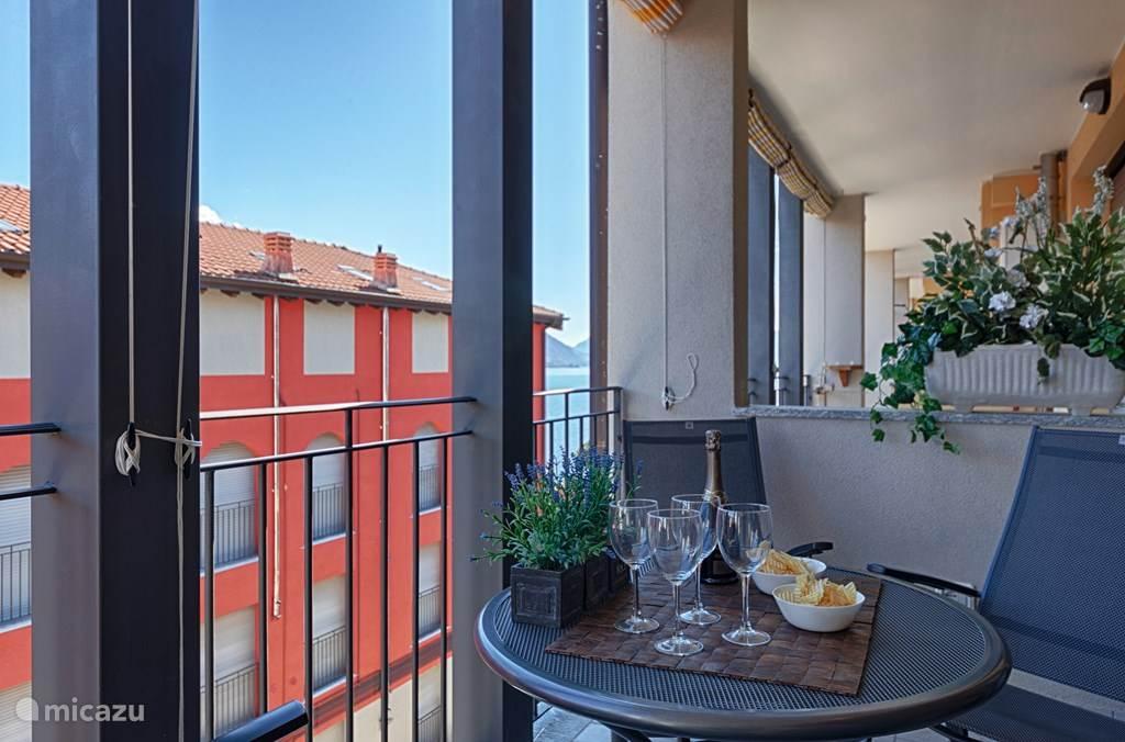 Het overdekte ruime balkon met comfortabel buitenmeubilair.