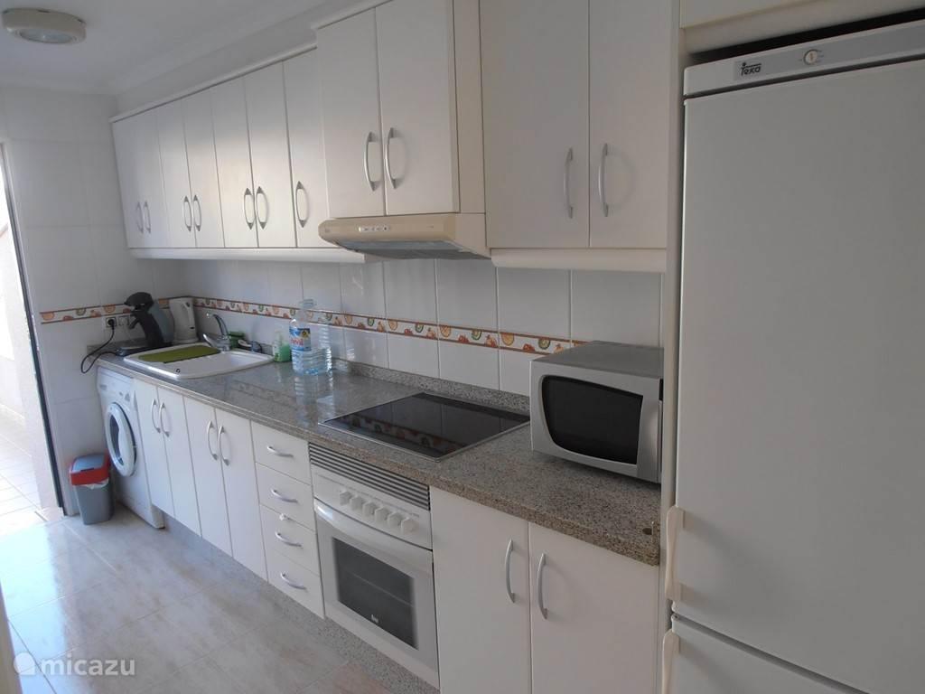 Ingerichte keuken met deur naar het achterterras