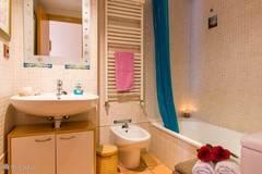 Badkamer met bad en handdouche