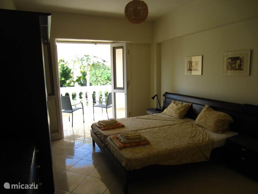 Master slaapkamer met balkon en privé badkamer.