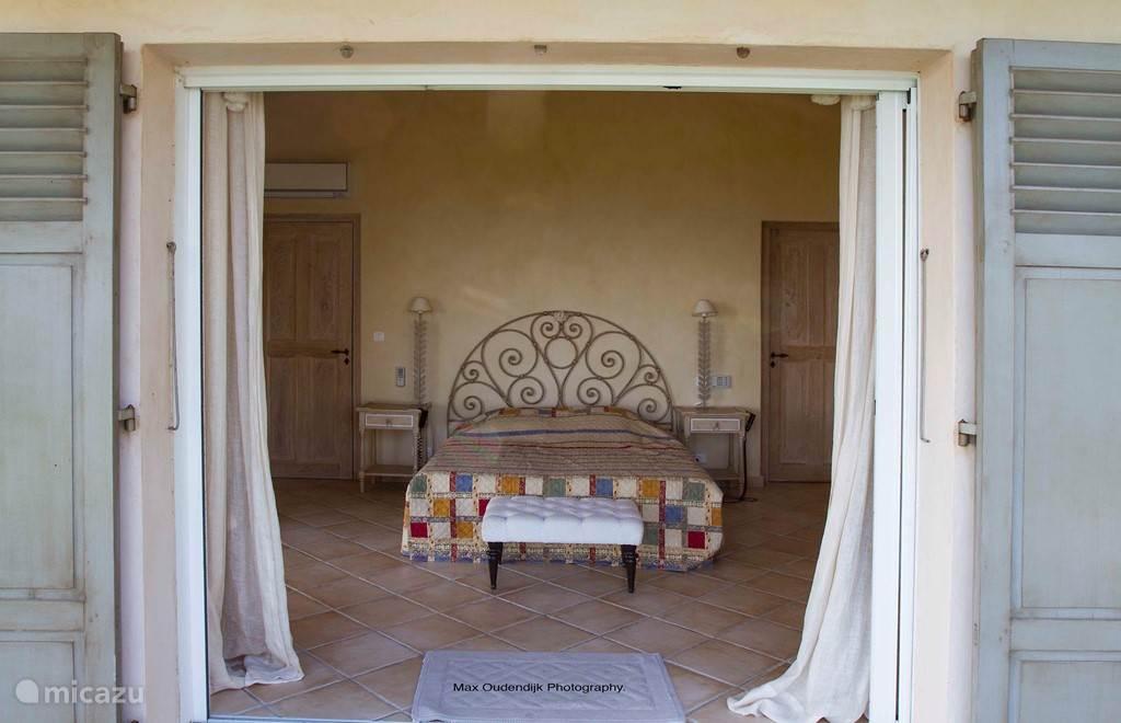 Slaapkamer met aangrenzend bad/douche en magnifiek uitzicht op terras en zee