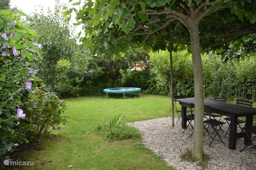 De weelderige tuin van De Boompjes waar u heerlijk kunt zitten en de kinderen kunnen spelen op de trampoline