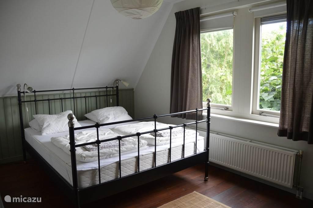 De grote slaapkamer met tweepersoonsbed