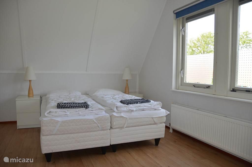 Slaapkamer met tweepersoonsbed en slaapbank