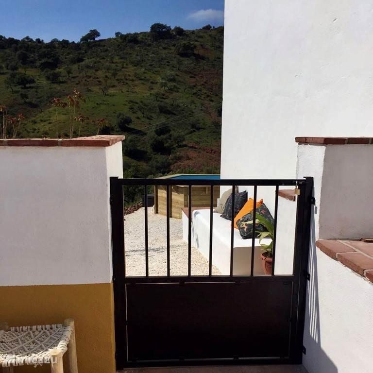 Aan de voorkant van het huis is een groot omheind terras. Hier kunnen je kinderen heerlijk en veilig spelen!