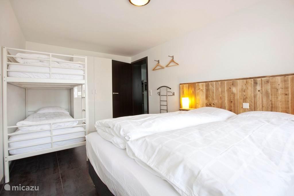 Appartement B met twee slaapkamers waarvan er een met een stapelbed en een twee persoons bed.