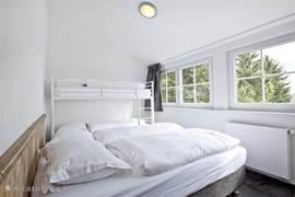 Appartement D sfeervolle vierpersoons slaapkamer voor twee volwassenen en een stapelbed.