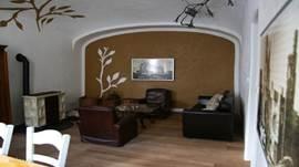 Gezellige woonkamer met houtkachel en ruime eethoek.