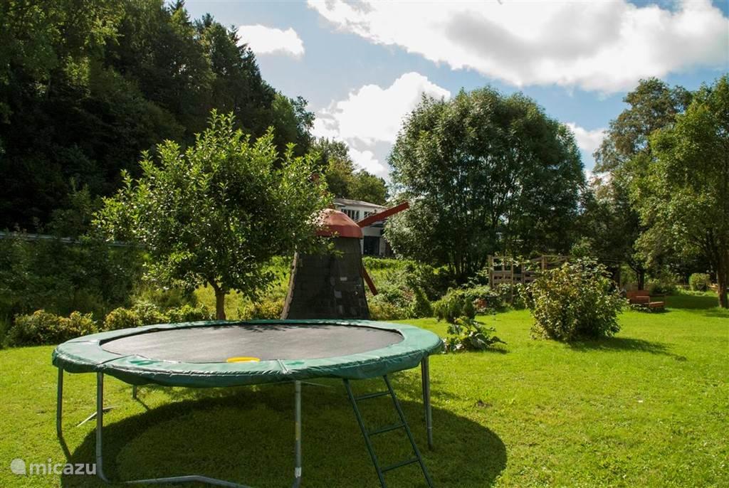 In de tuin een grote trampoline voor de kinderen.