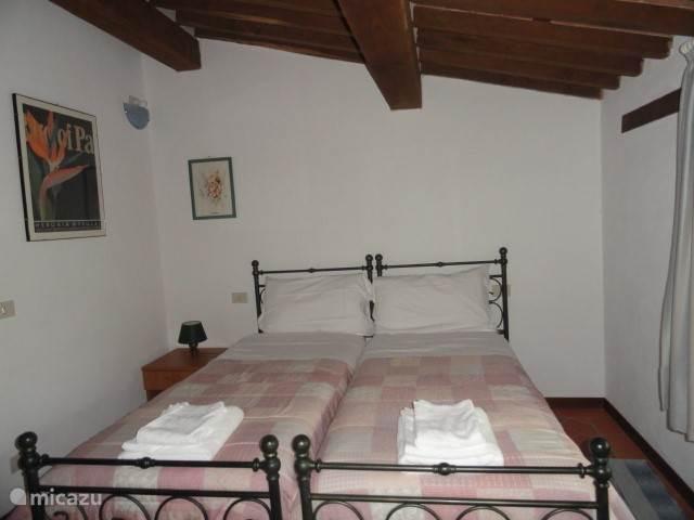 Een van de vier slaapkamers, waarvan drie met 2 enkele bedden, één met een queen -size-bed