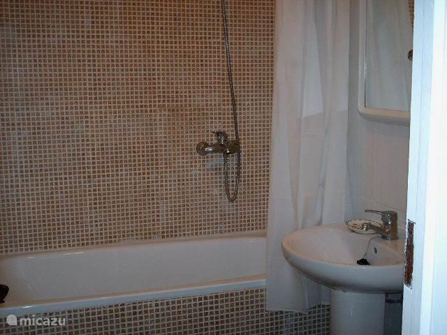 Badkamer met bad en douche boven.