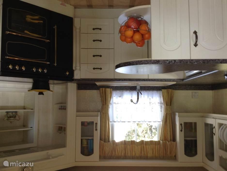 De keuken met gasfornuis, oven en vaatwasser.
